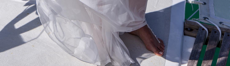 Nackte Fuesse einer Braut auf dem Hochzeitskatamaran.