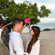 Verliebtes Paar zeigt auf ein Just married Schild im 4-Sterne Hotel Amsterdam Manor Beach Resort in Aruba.
