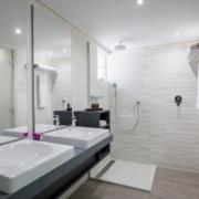 Badezimmer mit Doppelwaschbecken und Dusche im 4-Sterne Avila Beach Hotel auf Curacao.