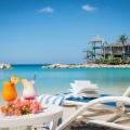 Hotelstrand mit Liege und Cocktails und Blick auf den Aussichtsturm im 4-Sterne Avila Beach Hotel auf Curacao.