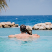 Verliebtes Paar im Infinity Pool im 4-Sterne Avila Beach Hotel auf Curacao.