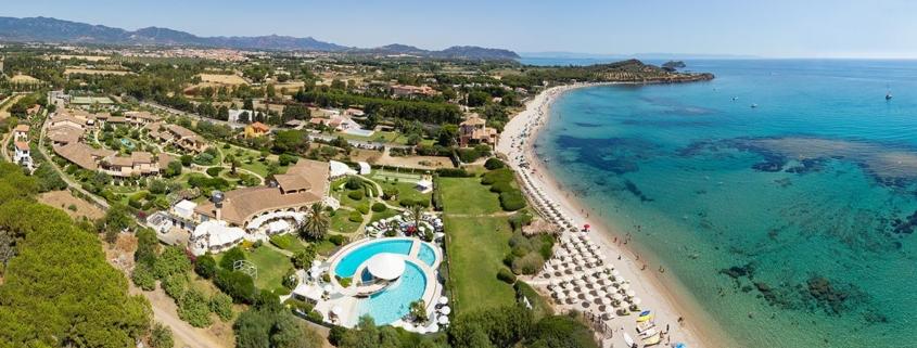 Luftaufnahme der Anlage mit großem Pool und Strand des 4-Sterne Hotels Baia di Nora in Pula auf Sardinien.