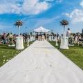 Brautpaar mit Hochzeitsgesellschaft im Garten des 4-Sterne Hotels Baia di Nora in Pula auf Sardinien.