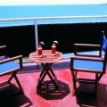 Balkon mit Regiestuehlen und Cocktails auf einem Zimmerbalkon im 4-Sterne Hotel Blue Haven auf Tobago.