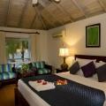 Doppelbett und Sessel in einem DeLuxe Zimmer Pool mit Steinen eingefasst und Liegen unter Palmlen im 4-Sterne Hotel Blue Haven auf Tobago. Frau steht auf dem Balkon und geniesst die Aussicht.