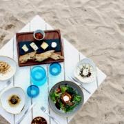 Aufnahme von oben auf einen gedeckten Tisch am Strand im 4-Sterne The Calabash Hotel auf Grenada. Salat, gegrillter Fisch und Käaeseauswahl mit Baguette.