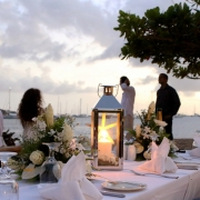 Brautpaar am Meer vor einem hochzeitlich dekorierten Tisch am Stand zum Abendessen im 4-Sterne The Calabash Hotel auf Grenada.