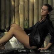 entspannte Frau lehnt an Buddah im Spa Innenansicht im Hotel Cannonier Beachcomber auf Mauritius