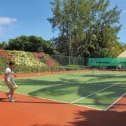 Tennisspieler auf dem Aussenplatz im 4-Sterne Canonnier Beachcomber Golf Resort & Spa.