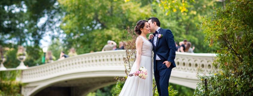 Brautpaar vor der Bow Bridge im Central Park in New York. Der Mann kuesst die Braut. Im Hintergrund unscharf gezeichnete Personen auf der Bruecke.