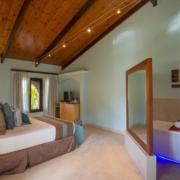 Zimmer mit Doppelbett im 5-Sterne Hotel Coco de Mer & Black Parrot Suites auf der Insel Praslin, Seychellen.