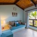Zimmer mit Couch und Blick in den Garten im 5-Sterne Hotel Coco de Mer & Black Parrot Suites auf der Insel Praslin, Seychellen.