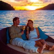 Junges, verliebtes Paar trinkt Champagner im Sonnenuntergang am Strand vom 5-Sterne Resorts Constance Ephélia in Mahe, Seychellen.