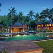 Blick ueber den Pool auf die Wohngebaeude im 5-Sterne Resorts Constance Ephélia in Mahe, Seychellen in der Abendstimmung.