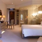 Innenansicht eines Tropical Garden Rooms im 5-Sterne Resorts Constance Ephélia in Mahe, Seychellen. Doppelbett; Verglastes Ndezimmer mit Dusche, Couch und Flachbildfernseher.