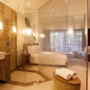 Blick aus dem verglasten Badezimmer auf Bett und Balkon im 5-Sterne Resorts Constance Ephélia in Mahe, Seychellen.