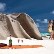 Junges Paar geht am Strand zu einem Picknickplatz mit Bento-Box und Champagner.