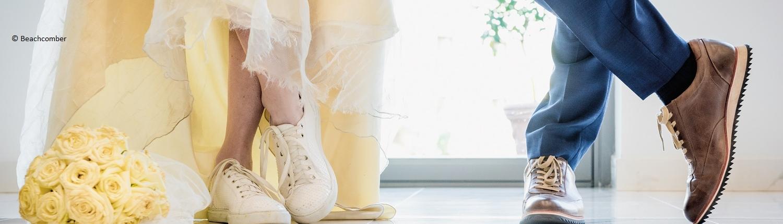 Laessiges Brautpaar, BRaut mit Turnschuhen, Braeutigam mit laessiger Haltung. Man Sieht nur die Beine und Schue. © Copyright bei Beachcomber Gruppe.