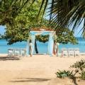 Der Hocheitspavillion steht am weissen breiten Sandstrand im 4-Sterne Couples Negril auf Jamaica. Fuer die Hochzeit geschmueckt mit Blumenbouquets und Gazeschleiern. Weisse Holzstuehle fuer die Hochzeitsgesellschaft.