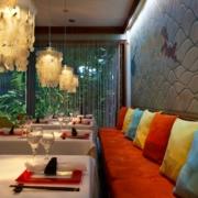 Restaurant im 4-Sterne Couples Negril auf Jamaica. Gemuetliche Baenke mit farbigen Kissen, stylische Lampen. Tische sind gedesckt fuer ein asiatisches Dinner mit Essstaebchen.