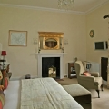 Innenansicht eines Zimmers mit Kamin und Blick in den Garten im 4-Sterne Cringletie House Hotel in Peebles Schottland.
