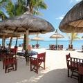 Strandrestaurant, Tische unter Sonnenschirmen im 6-Sterne Hotel Dinarobin Beachcomber Golf Resort und Spa auf Mauritius.