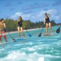 Stand-up-Paddler am Strand des Dinarobin Beachcomber Golf Resort und Spa.