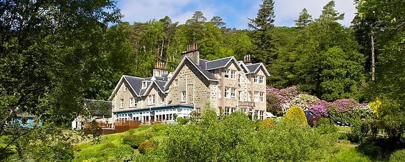 Aussenansicht auf das 4-Sterne Hotel Duisdale House auf der Isle of Skye in Schottland. Aufnahme im Sommer mit bluehenden Strauchern.