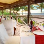 Restaurant am Strand mit weisssen Tischdecken und Stuhlhussen im 4-Sterne Galley Bay Resort und Spa auf Antigua.