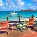 Sonnendeck mit bunten Holzschaukelstuehlen mit Blick auf das Meer und den Katamaran im 4-Sterne Galley Bay Resort und Spa auf Antigua.
