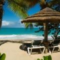 Liegen unter Sonnenschirm am Strand im 4-Sterne Galley Bay Resort und Spa auf Antigua.