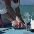 Brautpaar schneidet Hochzeitstorte an auf dem Katamaran in Mauritius.