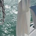 Brautkleid zum Trocknen aufgehaengt auf dem Katamaran nach Sprung ins Meer in Mauritus nach der Trauung.