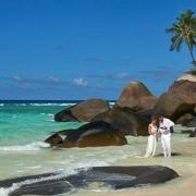 Brautpaar steht im Wasser und trinkt Champagner im 5-Sterne Hilton Seychelles Labriz Resort & Spa auf der Privatinsel Silhouette Island.