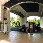 Paar kommt in der Eingangshalle des 5-Sterne Hotel Hilton Mauritius Resort und Spa und wird von Mitarbeiterin begruesst.