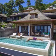 Grand Ocean Villa von ausssen mit privatem Pool im 5-Sterne Hilton - Northolme Resort & Spa auf den Seychellen. Mann springt ins Wasser, Frau liegt auf Liege.