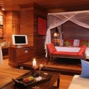 Blick in eine grosszuegige Villa mit Doppelbett und Moskitonetz des 5-Sterne Hilton - Northolme Resort & Spa auf den Seychellen.