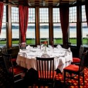 Runder Tisch mit Hochzeitsdekoration und Blick auf den See im 4-Sterne Bunchrew House Hotel in Inverness in Schottland.