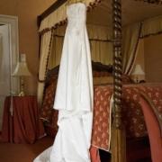 Himmelbett mit aufgehaengtem Brautkleid im 4-Sterne Bunchrew House Hotel in Inverness in Schottland.