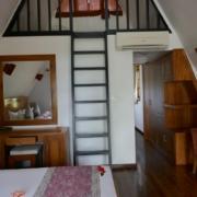Innenansicht des Zimmers Doppelbett mit Blumen geschmueckt im 3-Sterne plus Hotel La Digue Island Lodge auf den Seychellen.