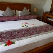 Doppelbett mit Blumen geschmueckt im 3-Sterne plus Hotel La Digue Island Lodge auf den Seychellen.