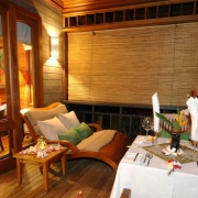 Balkon einer Villa im 5-Sterne Hilton - Northolme Resort & Spa auf den Seychellen. Romantisch mit Blumen gschmueckter Tisch am Abend.