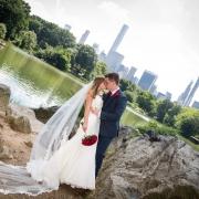 Brautpaar kuesst sich im Central Park am See mit der Skyline von New York im Hintergrund.