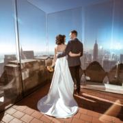 Brautpaar haelt sich im Arm nach der Trauung auf dem Rockefeller Center in New York.