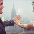 Eine Blonde Braut mit Stirnband und ihr Ehemann mit weisser Rose am Revers halten die Haende mit Trauringen in die Luft auf dem Rockefeller Center in New York.