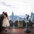Braeutigam kuesst Braut auf Wange auf dem Rockefeller Center anch der Trauung. Im Hintergrund die Skyline von New York.