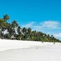 Weisser, einsamer Sandstrand mit Fischerboot vor dem 4-Sterne Ocean Paradise Resort.