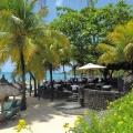 Blick auf den Strand mit Liegen und Sonnenschirmen und der Bar im 6-Sterne Hotel Royal Palm Beachcomber auf Mauritius.