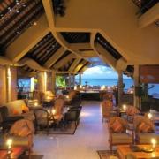 Aufenthaltsbereich und Bar mit Blick auf das Meer in der Abenddämmerung im 6-Sterne Hotel Royal Palm Beachcomber auf Mauritius.