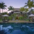 Blick über den Pool auf das Hauptgebaeude im 6-Sterne Hotel Royal Palm Beachcomber auf Mauritius in der Abenddaemmerung.